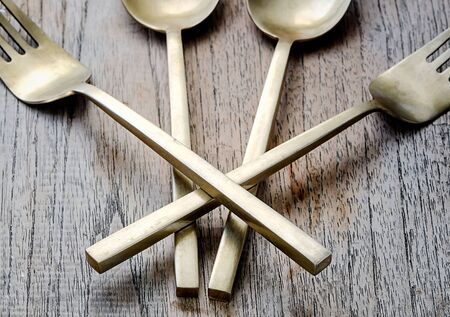 houseware: Old brass spoon and fork on wooden background,soft focus Stock Photo
