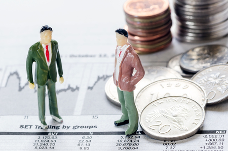 news paper: Coins and mini model of business man on news paper,for finance concept.