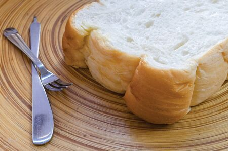 food stuff: Slice of white bread on bamboo plate,soft focus.