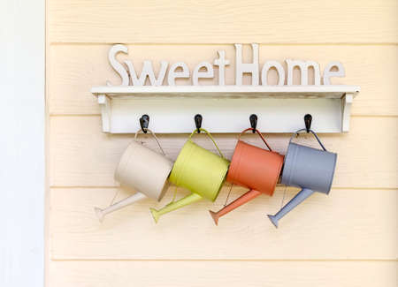 watering pot: SweetHome sign with small watering pot hang on the wooden wall.