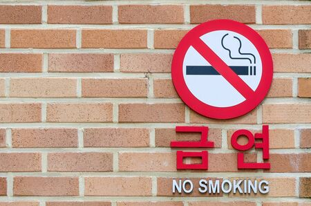permitted: No smoking sign hangs on a brick wall warning that smoking is not permitted in the area.