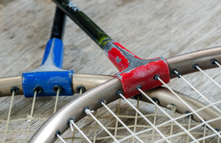 close up view: Old badminton racket on wooden background in close up view.