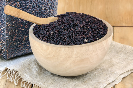 Closeup of raw purple Riceberry rice in wooden blow on wooden background.