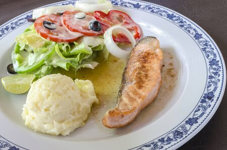 meat diet: Salmon steak with mashed potatoes and vegetables salad Stock Photo