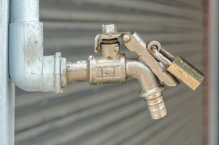 prevent: Old faucet  with padlock prevent water theft. Concept of save water.