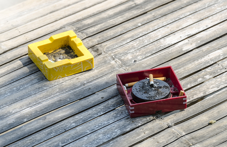 out door: Red and yellow ashtrays on bamboo table out door.