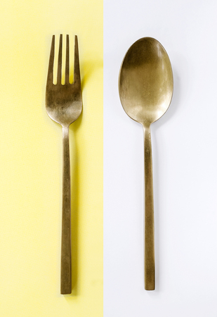 houseware: brass spoon and fork  on half yellow and white background Stock Photo