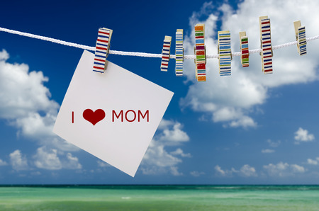 peg: White note with word hang on the rope with wooden peg under blue sky.Mothers Day concept.