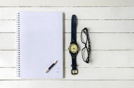 blank note book: Blank note book , pencil ,watch and eyes glass on wooden background.