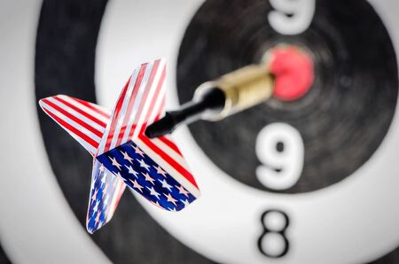 Dart arrow with usa flag  hitting in the target center of dartboard,shallow DOF Stock Photo