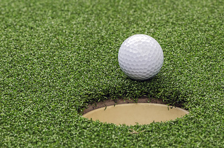 caddie: Golf  ball on lip of cup,close up view.