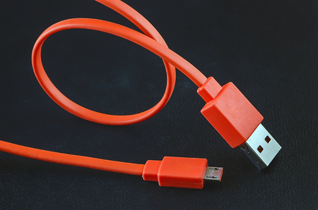 input device: Orange color USB cable on black leather background. Stock Photo