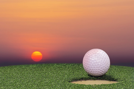 caddie: Golf  ball on lip of cup with the sunset background.
