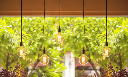 indoor background: Warm tone light bulb lamps hang against  day light out side the window.
