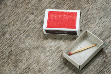 match box: one match in the box on wooden background.