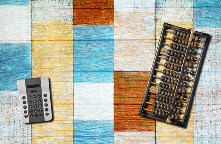 An old chinese abacus and modern calculator on blue wooden background. Reklamní fotografie