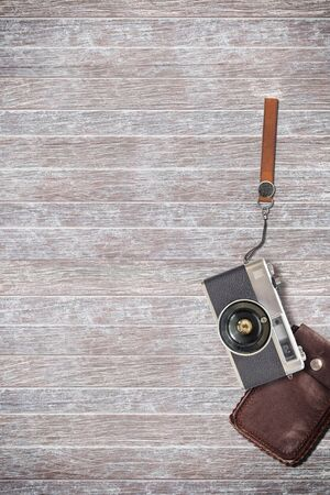 leather bag: vintage camera and leather bag on wooden background. Stock Photo