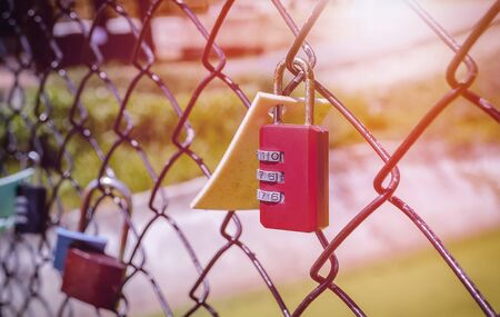 Old and rusty red padlock hanging on metal fence