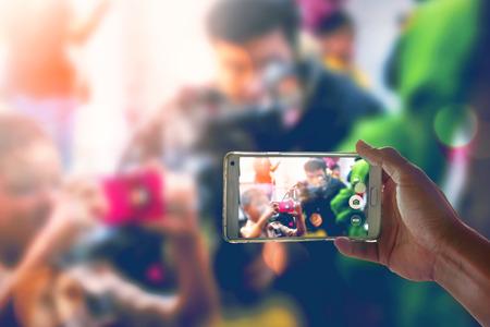 Persona está tomando video con un teléfono inteligente. Foto de archivo - 73855077