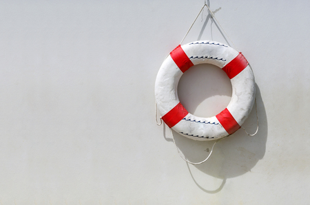 Old life buoy hanging on white concrete wall for emergency response