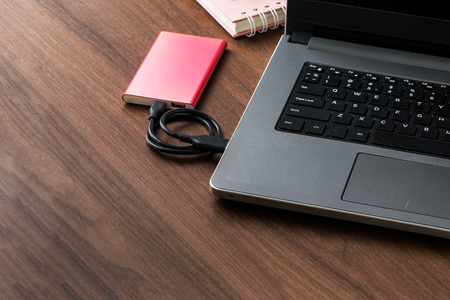 Red external hard drive (HDD) connected to laptop for transfer or backup data on wooden desktop with copy space Stock Photo