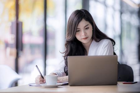 Mujer de negocios asiática joven que usa la computadora portátil y escribe en el cuaderno, oficial de la mujer que trabaja duro se comunica con el cliente y registra