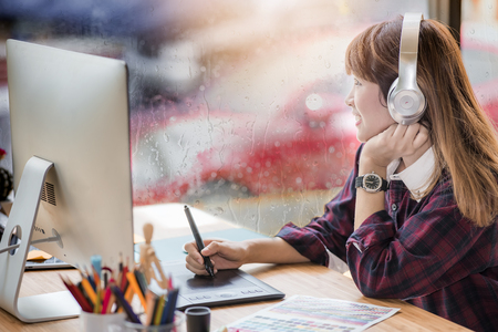 beautiful young woman designer listening music with headphone while using pen mouse working in office with raining day outside Archivio Fotografico