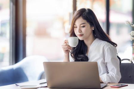 Mujer asiática del negocio joven que sostiene la taza de café y que mira el ordenador portátil, café de la bebida del oficial de la mujer en el tiempo de la rotura. Foto de archivo