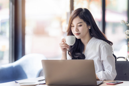Young business asian woman holding cup of coffee and looking at laptop,woman officer drink coffee at break time.