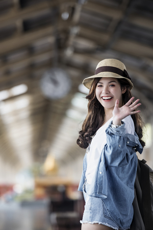 Asian backpack traveler woman smiling and waving hand at train station platform, summer holiday travelling or young tourist concept