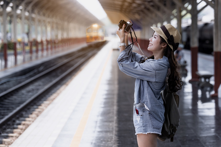Young beautiful woman traveler with backpack holding vitage camera and taking photos  at railway station Stock Photo