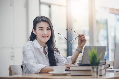 Portrait of beautiful businesswoman holding glasses and sitting at her desk in office. Foto de archivo