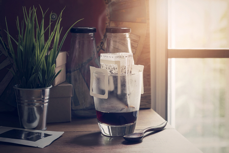 Instant freshly brewed cup of coffee or paper dripping bag on a cup on wooden table with sunlight in the morning