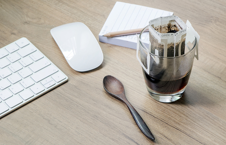 Instant freshly brewed cup of coffee or paper dripping bag on a cup on wooden table with computer keyboard and mouse