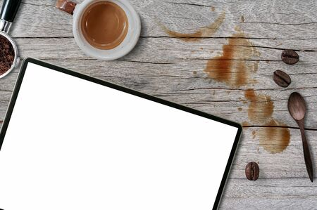 Top view blank screen tablet with cup of coffee, portafilter, coffee bean, wooden spoon and coffee stains on wooden top table background.