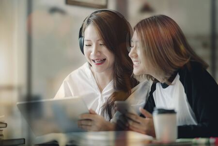 Two best friends using digital tablet together. Women sitting and having fun surfing on the internet using smart digital pc tablet modern device.