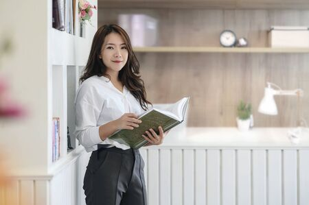 Attractive smiling businesswoman standing in modern office with boook in hands.