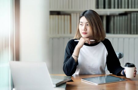 Portrait of pretty young businesswoman in casual wear holding stylus pen, looking outside and thinking while sitting in modern office.