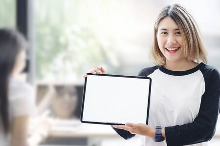 Casual smiling woman showing blank tablet computer screen while standing in bright room. Looking at camera