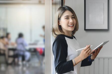 Attractive businesswoman using a digital tablet while standing in front of meeting room in an office building.