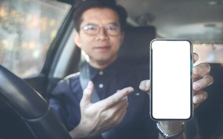 Man with eyeglasses showing blank screen smartphone while sitting in car. Stock fotó