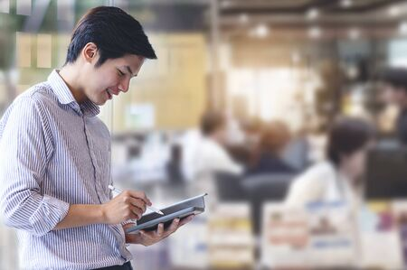 Young businessman in casual clothes working with tablet while standing in modern office.