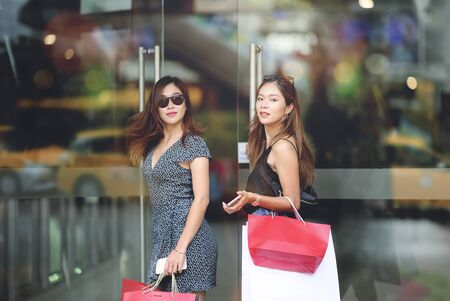 Two beautiful girls with sun glasses are holding shopping bags and smartphone standing at the shopping mall entrance with happiness.