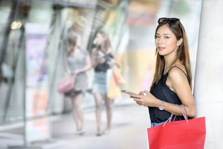 Portrait of young attractive woman with shopping bags using smartphone while shopping at the mall, smiling and looking at camera, shopping concept.