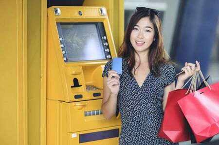 Beautiful asian woman with shopping bags holding credit card standing near yellow ATM machine and looking at camera. Stock fotó