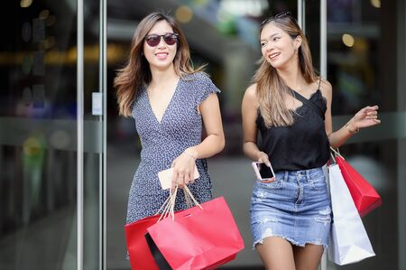 Beautiful girls with sun glasses are holding shopping bags and smartphone walking out of the mall with happiness. Stock fotó