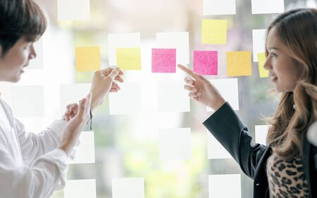 Business people pointing at  multi colored sticky notes on glass in meeting room at creative office.