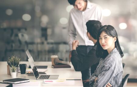 Young female designer with arms crossed looking at camera while sitting at her desk office. Group of designers in casual clothes working in studio. Stock fotó