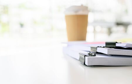 Stack of white paper with black clips clamped and cup of coffee on white table, focus on paper, shalow DOF.