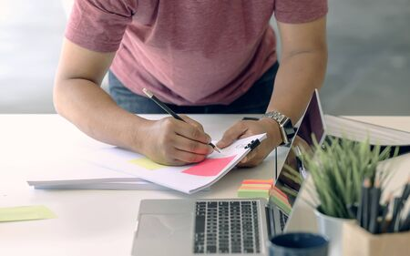 man in casual wear using pencil writing on white paper with sticky note while working at home office.